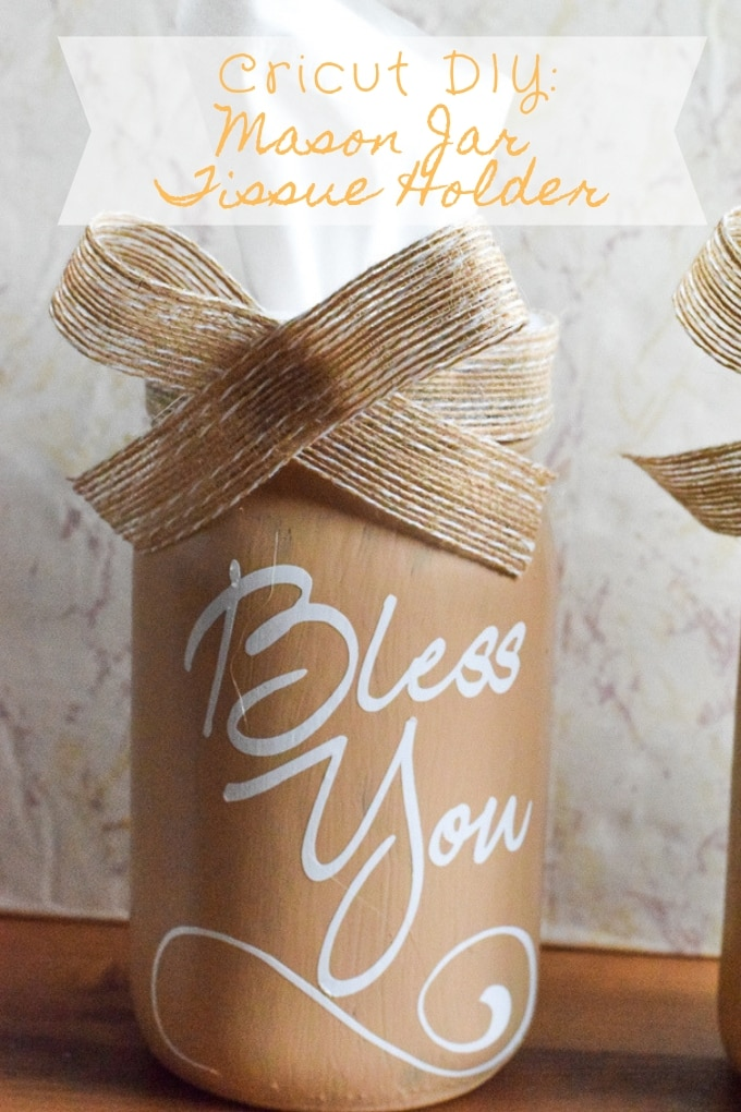"A mason jar tissue holder painted with cream chalk paint and with the words ""bless you"" written on the front in vinyl."