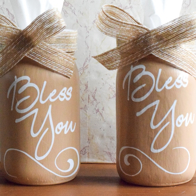 "Two mason jar tissue holders painted beige with the words ""bless you"" written on front."