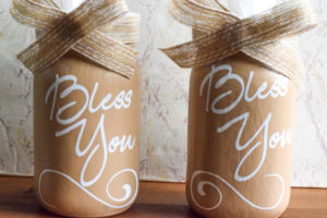Two mason jars made into mason jar tissue holders and decorated with a ribbon bow.