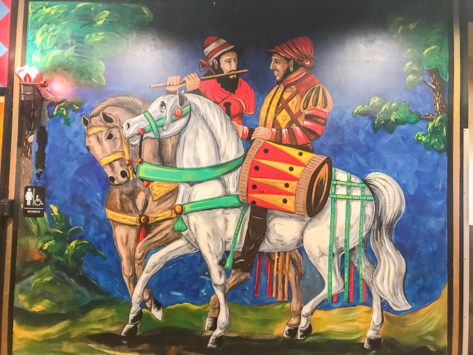 A mural of two knights on horses painted on a wall at Medieval Times.
