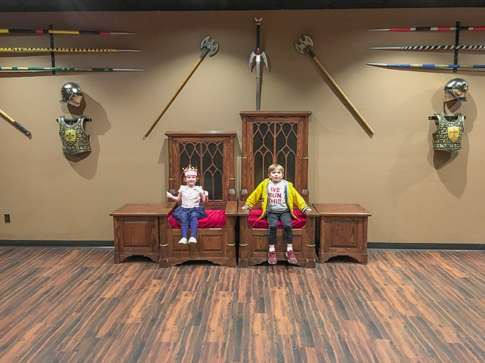Two kids sitting in the king and queen thrones at Medieval Times Buena Park.