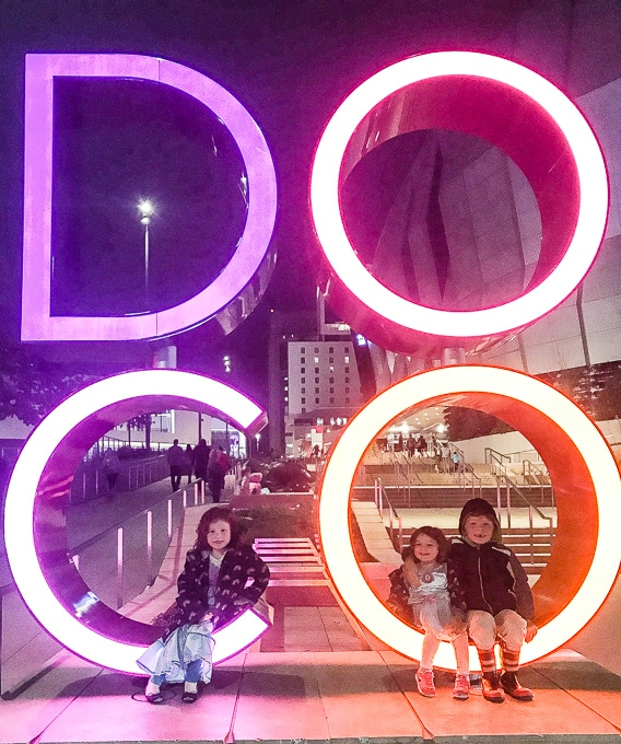 Three kids sitting on a lit up statute in front of the Golden 1 Center.