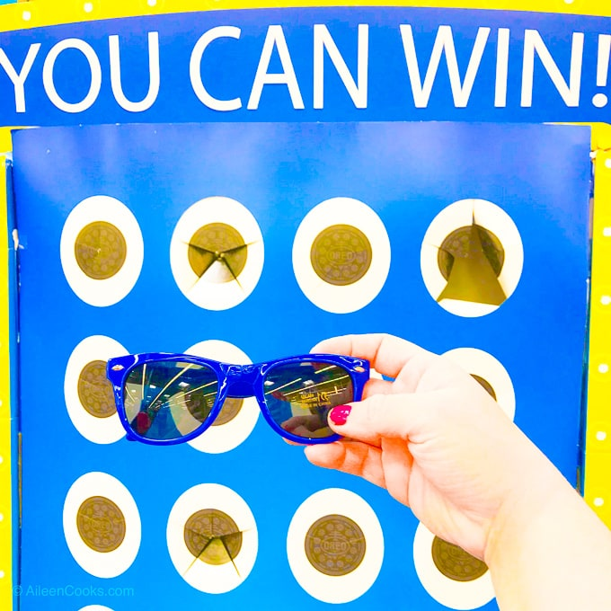 "A hand holding a pair of blue sunglasses in front of a blue and yellow game that says ""you can win""."