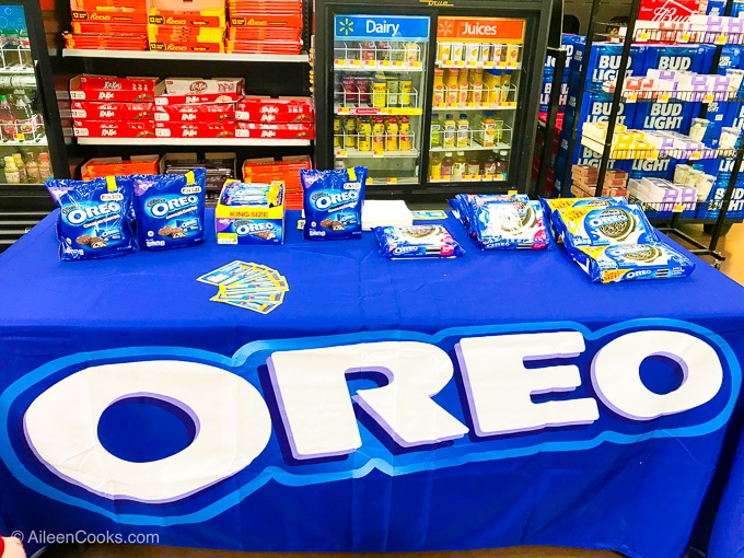 A table set up with a blue OREO tablecloth and topped with various OREO cookies.