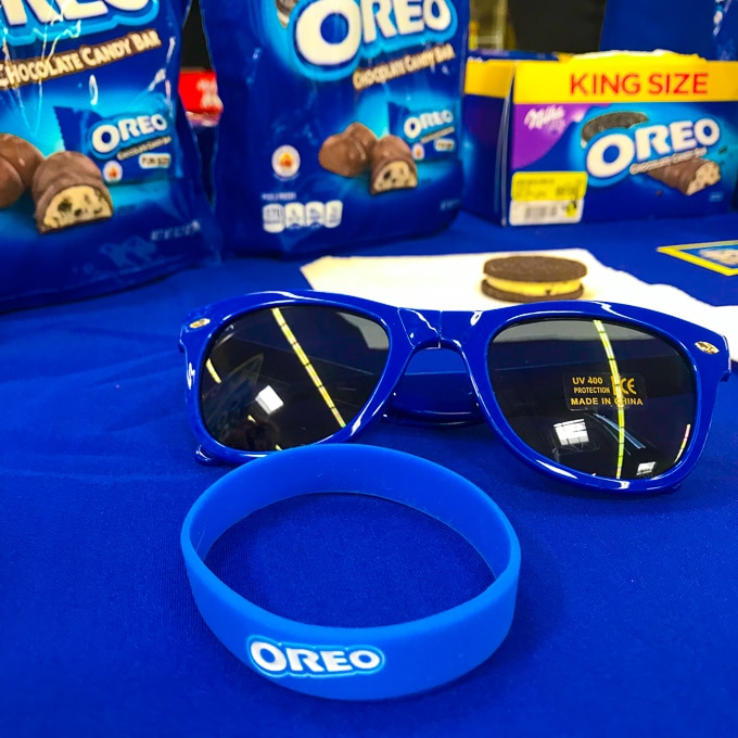 An OREO bracelet and sunglasses on a blue tablecloth.