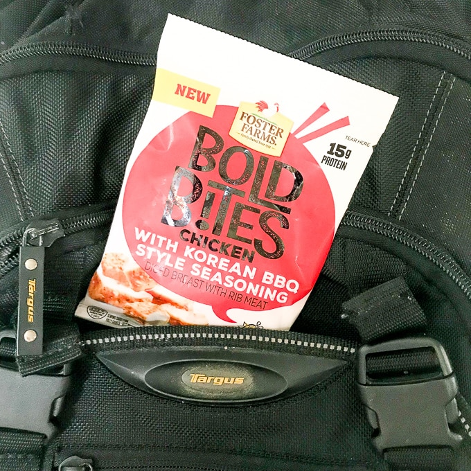 Close-up of a black backpack with a bag of Foster Farms Bold Bites Korean BBQ peaking out of the pocket.