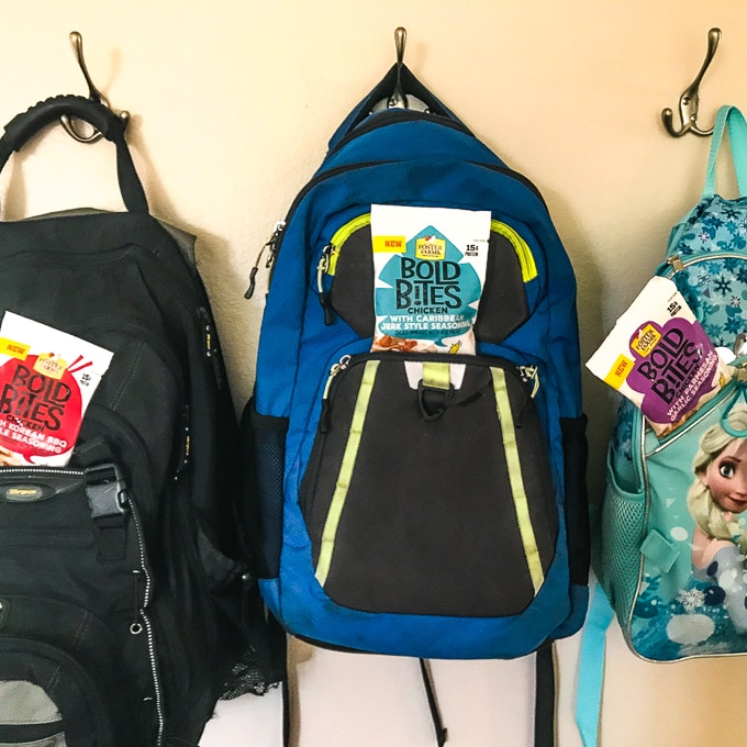 Three backpacks hanging on a wall, all with Foster Farms Bold Bites in the front pocket.