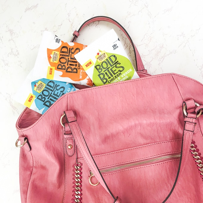 A large pink purse with three bags of Foster Farms Bold Bites poking out the top of the bag.