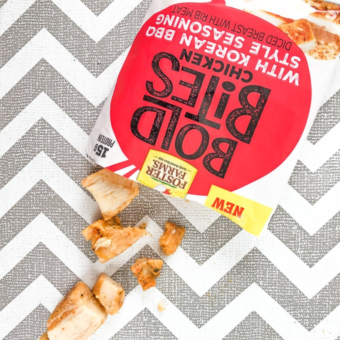 An opened bag of Korean BBQ Bold Bites spilling out on the to the grey and white zig zag background.