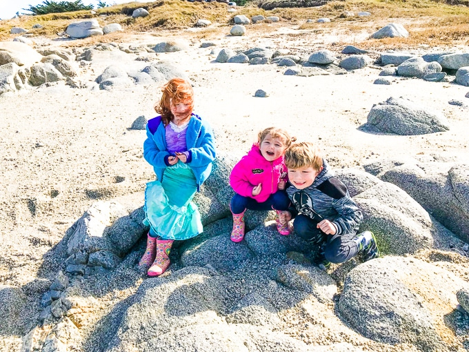 Three kids on the beach in Pacific Grove.