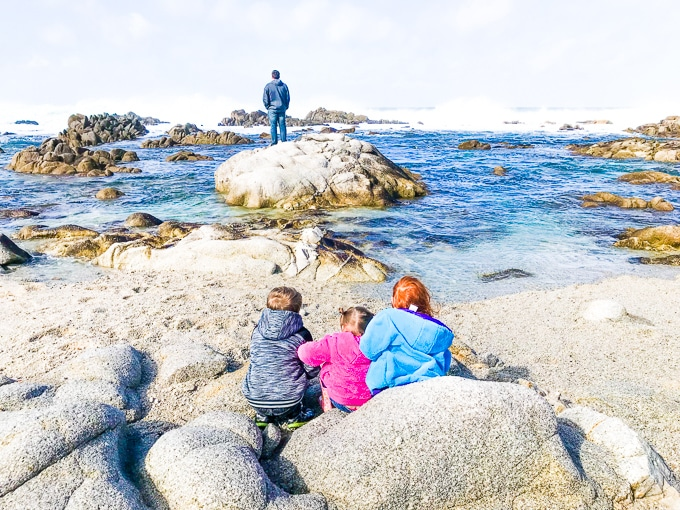 Three children sitting together and watching a man standing on a large rock in the ocean.