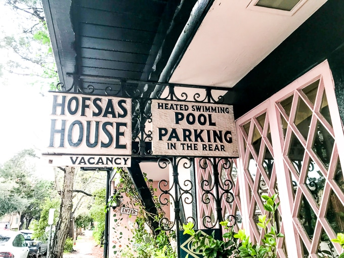 The two signs in front of Hofasa House, one advertising Hofsas House and the other advertising their pool and parking.