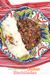 A festive plate on top of a red towel, filled with instant pot chicken enchiladas and beans.