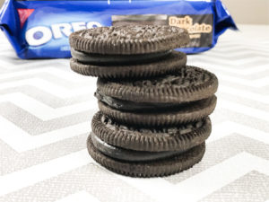 Three OREO Dark Chocolate cookies stacked up in front of the package.