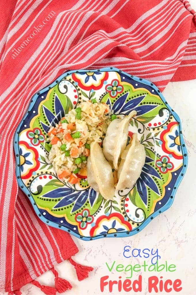 A colorful plate filled with fried rice and pot stickers, on top of a red striped towel.