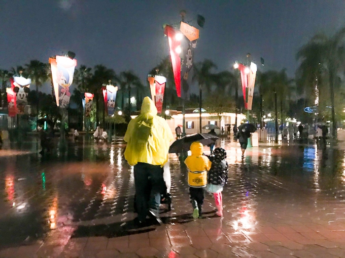 A man and his two children walking through Disneyland in the rain.