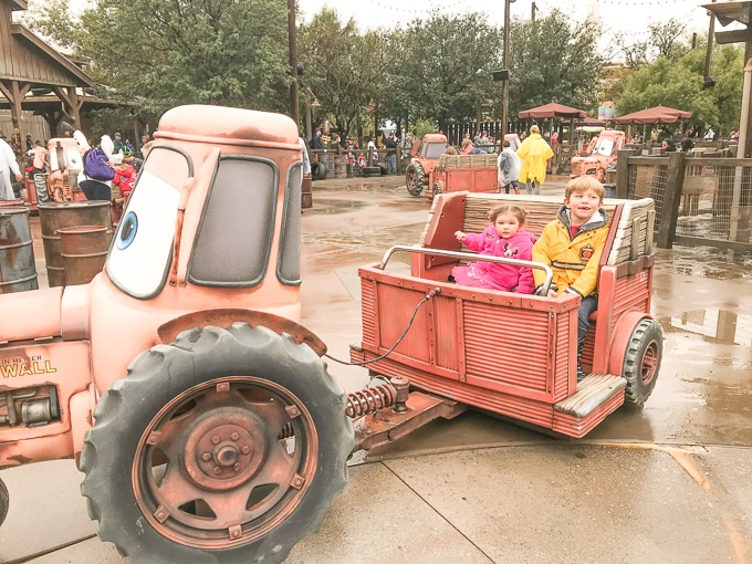 A boy and girl riding Mader's Junkyard Jamboree in California Adventure during Winter.