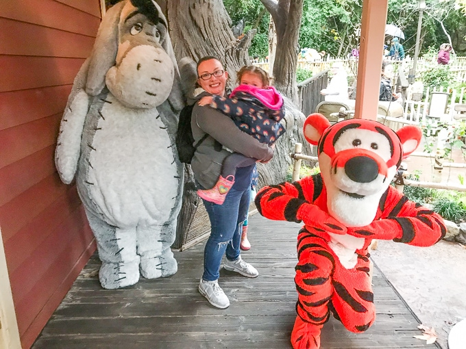 A little girl in her mom's arms next to Winne the Pooh and Tigger at Disneyland in Winter.