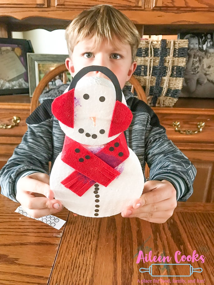 A boy holding a foam snowman with red ear muffs made from the Winter themed We Craft Box.