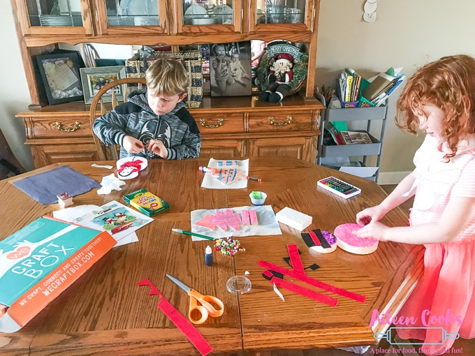 Two children sitting at a wooden table make winter crafts from We Craft Box.