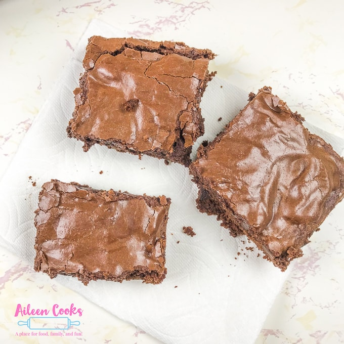 Three chocolate chunk brownies on top of a paper towel.