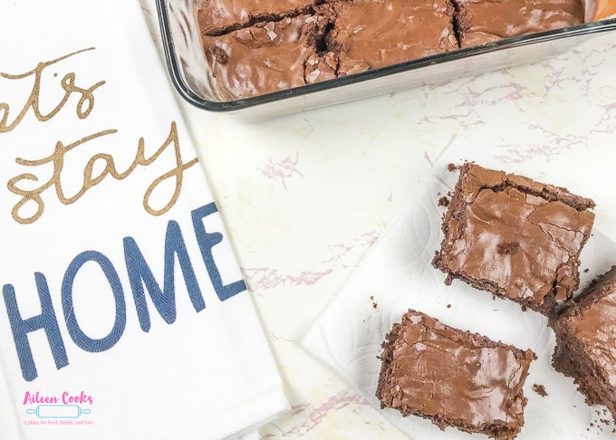 "A dish towel that says ""Let's stay home"" next to a batch of frosted chocolate chunk brownies."