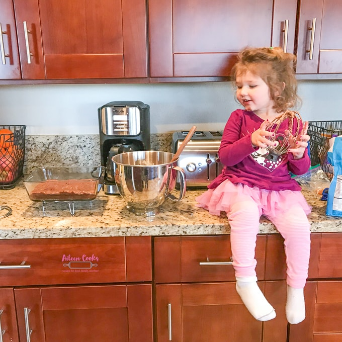 A little girl sitting on a kitchen counter holding a whisk covered in chocolate frosting, next to a batch of chocolate chunk brownies.