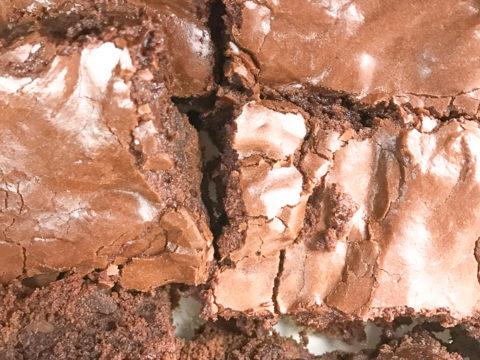 A close up of 6 frosted chocolate chunk brownies.
