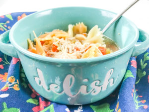 "A teal bowl with the words ""delish"" written on the front and filled with the instant pot chicken noodle soup recipe."