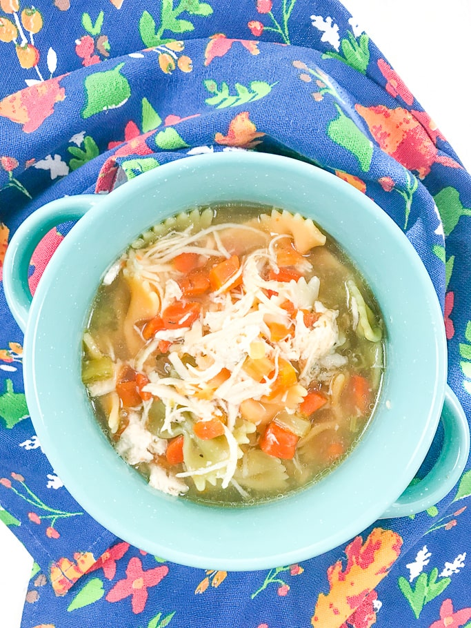 A bowl of chicken noodle soup filled with fresh carrots, celery, and bow tie pasta.