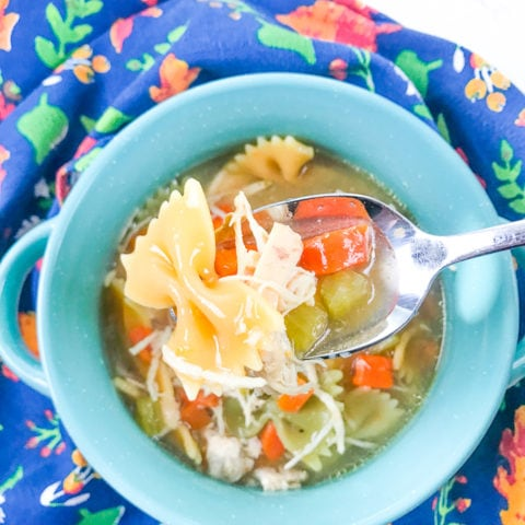 A bowl of the instant pot chicken noodle soup recipe with a spoon lifting up a bite.