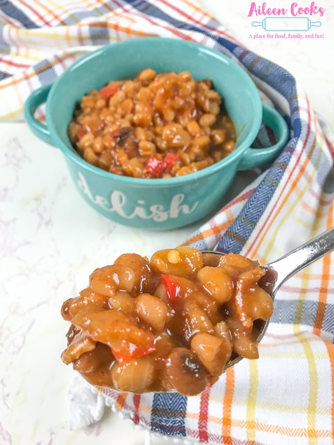 A spoonful of instant pot baked beans next to a bowl of beans.