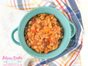 A teal bowl filled with instant pot baked beans.