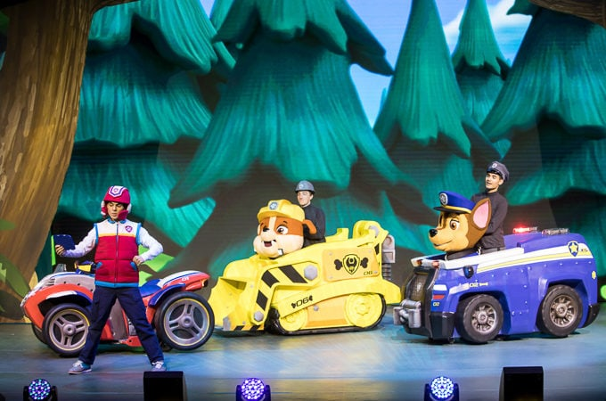 Three puppet dogs in toy cars on the Paw Patrol Live! stage.
