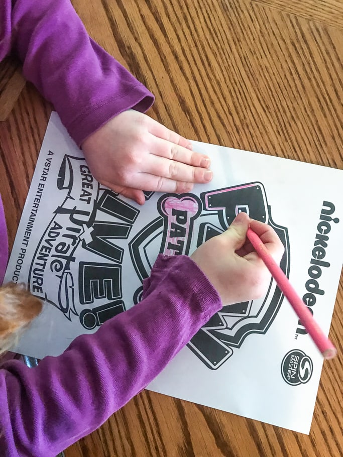 A little girl's hands coloring in a Paw Patrol Live! coloring page with a pink colored pencil.