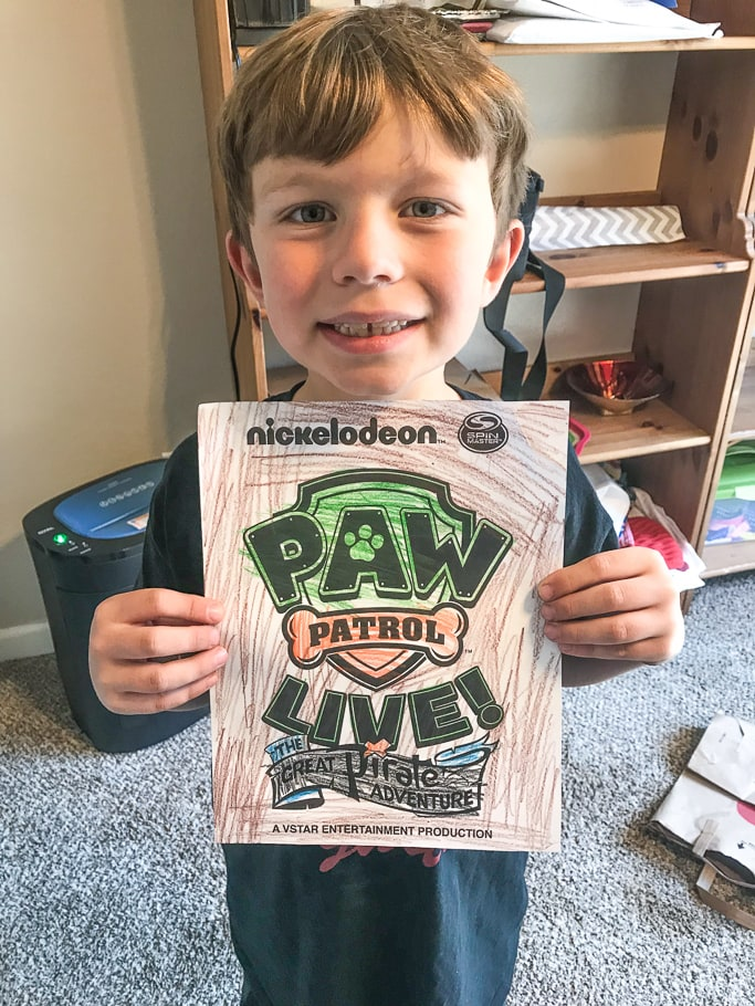 A boy holding his colored in Paw Patrol Live! coloring sheet.