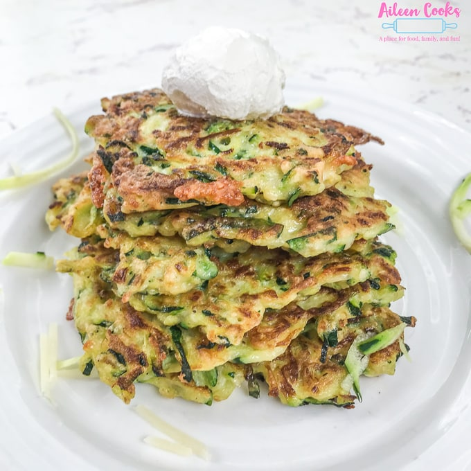 Zucchini fritters stacked up with sour cream on top.