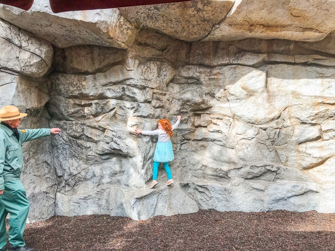 A red-headed girl climbing sideways on a rock wall.
