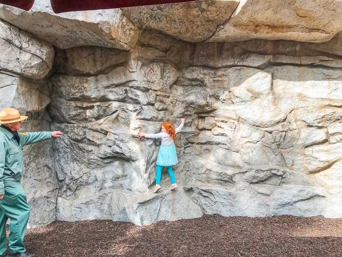 A red-headed girl climbing sideways on a rock wall.