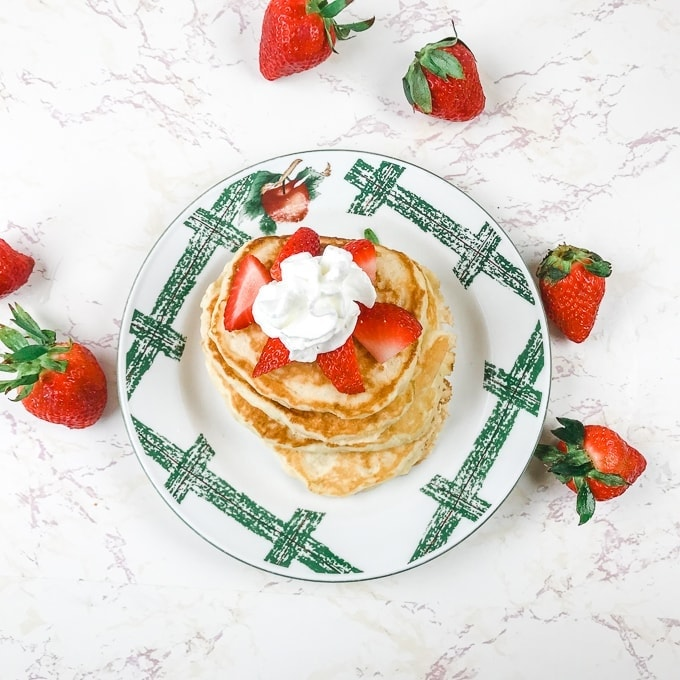A stack of pancakes topped with strawberries and whipped cream, surrounded by more strawberries.