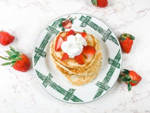 A plate with apples painted on it holding a stack of pancakes.