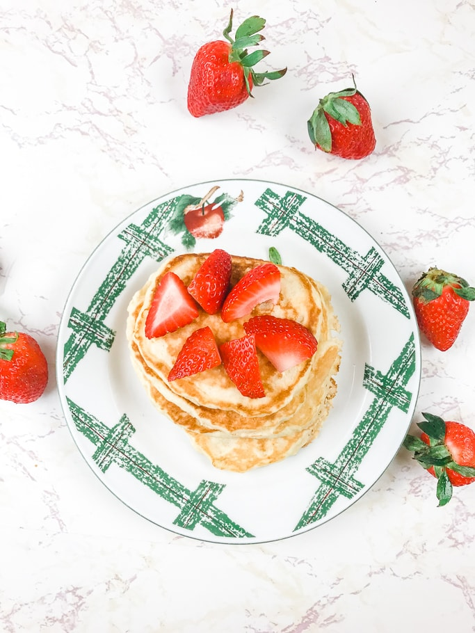 Overhead shot of pancakes topped with sliced strawberries.