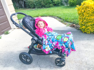 A little girl in a black stroller covered in a pink and blue fleece tie blanket.
