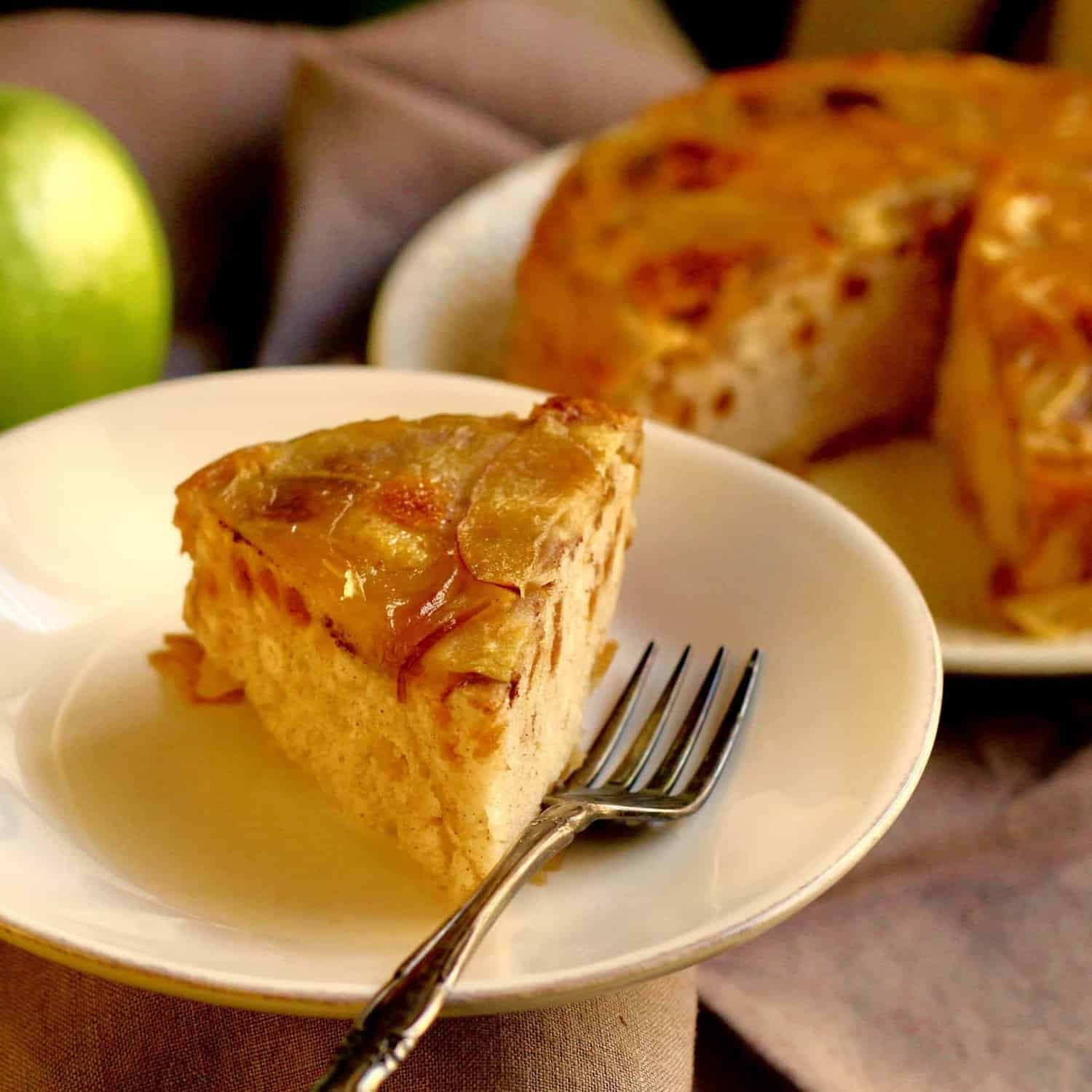 A slice of instant pot apple cake in front of the whole instant pot apple dessert.