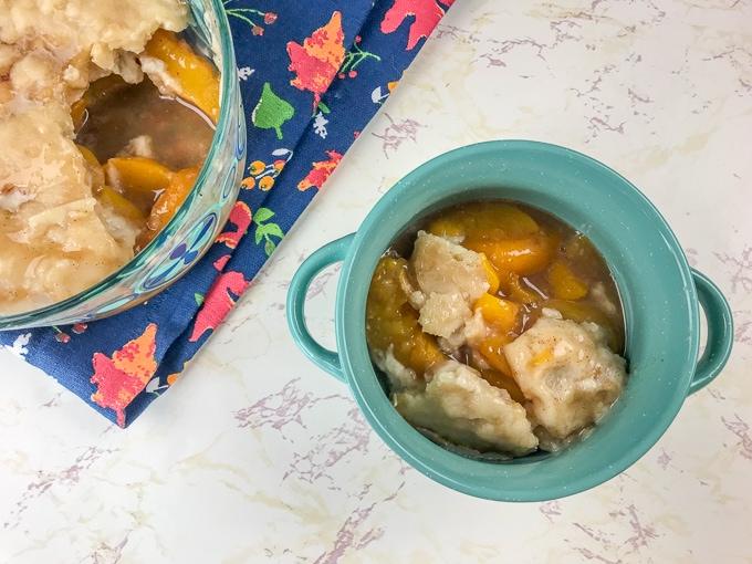 Bowl of instant pot peach cobbler with cake pan of peach cobbler in upper left hand corner.
