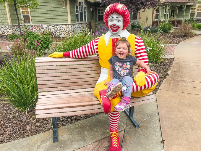 A little girl sitting on the Ronald McDonald statue at the Ronald McDonald House Charities in Sacramento.
