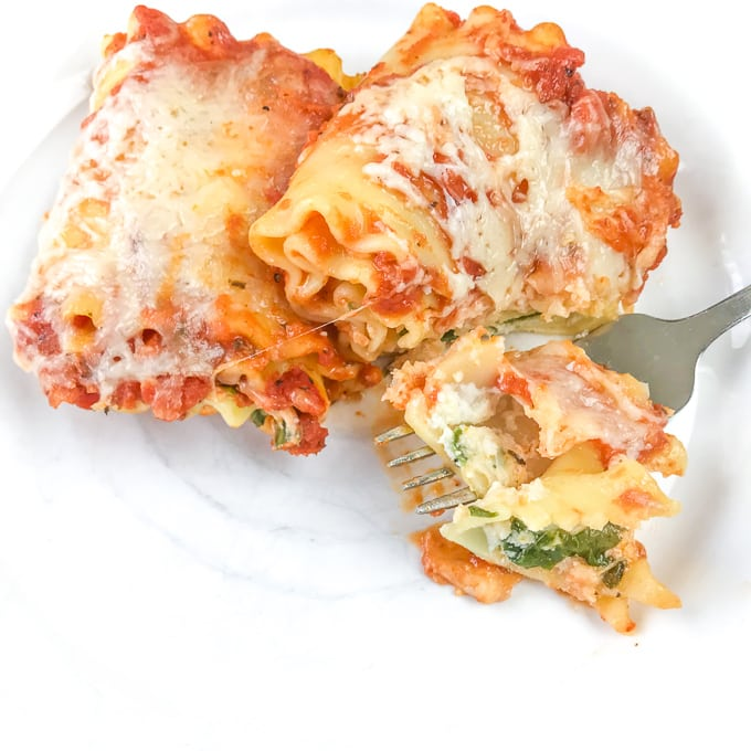 A bite of spinach lasagna roll-ups on top of a dinner plate.