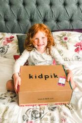 Little girl holding a Kidpik box.