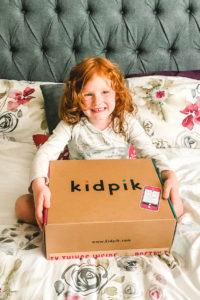 Little girl holding a Kidpik box.