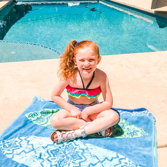 Little girl sitting on a towel in front of a pool, wearing a swim suit and shorts.